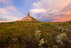 A scenic landscape photograph of the sunset and Chimney Rock National Historic Site. - Nebraska Photograph