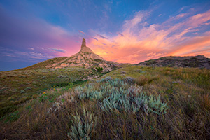 A scenic landscape photograph of a sunset and Chimney Rock National Historic Site. - Nebraska Photograph