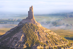Morning Fog surrounds Chimney Rock in western Nebraska at sunrise. - Nebraska Photograph