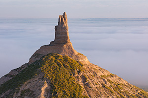A scenic landscape photograph of Chimney Rock National Historic Site in fog. - Nebraska Photograph