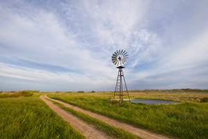 In an area of the Sandhills of Nebraska, far from civilization a two-track road meanders by a windmill and a lake nestled in the hills. - Nebraska Sandhills Photograph