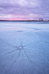 On this evening at DeSoto National Wildlife Refuge a quiet stillness prevailed.  I wandered the shore of the lake looking for interesting patterns in the now melting ice.  I found some interesting star shapes that had emerged from the recent thaws.  Sunset was near and although it was cloudy, I was hoping for a little illumination of the clouds.  After a while I gave up and begin leaving when a bit of sun broke free and I quickly set up again and captured this image. - Nebraska Landscape Photograph