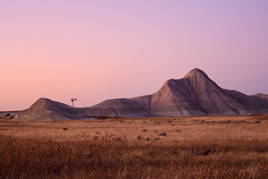 Scenic landscape photograph of a windmill and badlands during dusk in western Nebraska. - Nebraska Photograph