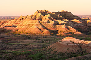 Light from the recently risen sun illuminates the Badlands in South Dakota with a warm orange hue. - South Dakota Photograph