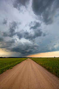 A landscape photograph of an intense summer storm rages over a rural country road in South Dakota. - South Dakota Photograph