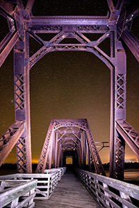 On a clear night at Niobrara State Park, I setup on the railroad trussle converted to a footbridge near the confluence of the Niobrara and Missouri Rivers.  Using a flashlight I lightpainted the bridge while exposing for the stars.  In the distance the lights of Niobrara can be seen glowing on the horizon. - Nebraska Photograph