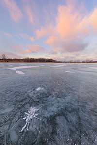 On a frigid January day clouds hover over the frozen Wehrspann Lake at Chalco Hills Recreation Area in Sarpy County, Nebraska. - Nebraska Photograph