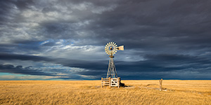 Scenic landscape panoramic photograph of a windmill and a storm at Oglala National Grasslands. - Nebraska Photograph