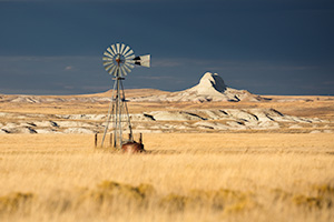 Scenic landscape panoramic photograph of a windmill and Sugarloaf Butte at Oglala National Grasslands. - Nebraska Photograph