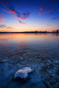 This photograph was captured in the dead of winter, when the old Missouri River oxbow at DeSoto National Wildlife Refuge transforms into a reflective sheet of ice with a single rock still visible. - Nebraska Photograph