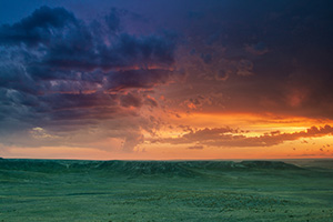 The verdant prairie grass appears as a green carpet in the valleys of Agate Fossil Beds National Monument in western Nebraska as the last bit of sunlight radiates from beneath the dark storm clouds.  From a high perch, I watched this storm as it moved past, the clouds changing and morphing. - Nebraska Landscape Photograph