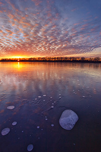 The warm setting sun shines brightly across the frozen lake on a chilly January evening before dipping below the horizon. - Nebraska Landscape Photograph