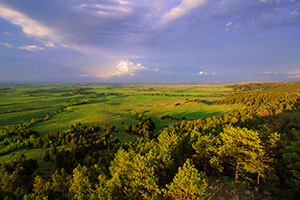 In the extreme Northwestern edge of Nebraska from high on the pine ridge escarpment the afternoon sun warms the rain drenched plains below. - Nebraska Landscape Photograph