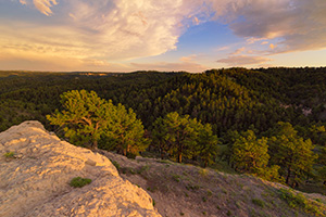 In the extreme Northwestern edge of Nebraska, north of Harrison is a little WMA called Gilbert-Baker WMA.  On this cool spring evening, I hiked for a couple of miles over a few hills and then sat on this rock content to eat my dinner and watch a storm brew in the distance and then dissipate, leaving interesting clouds to reflect the light of the setting sun. - Nebraska Landscape Photograph