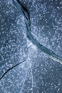 Deep cracks form in the ice from frigid cold weather on Lake Wehrspann at Chalco Hills, Nebraska. - Nebraska Photograph