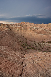 As a storm passes over Badlands National Park in South Dakota, dark clouds contrast with the desolate landscape. - South Dakota Photograph
