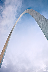 Built between February 12, 1963, and October 28, 1965 the Gateway Arch in St. Louis was designed to honor the westward expansion of the United States.  Designed by architect Eero Saarinen and engineer Hannskarl Bandel, it is 630 feet wide at its base and 630 feet tall and is currently the tallest monument in the United States.  From the base of the north leg looking in a south easterly directly, the structure curves through the sky almost touching the low clouds.  - Missouri Photograph