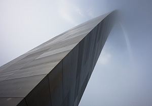 From the base of the north leg looking in a south easterly directly, the Gateway Arch curves through the sky and into the fog.  - Missouri Photograph