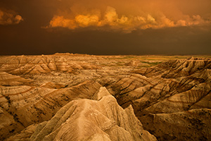 Facing east, the sky was nearly pitch black shrouded by the fierce storm that had just passed through.  As the sun dipped below the horizon the last rays hit the trailing storm clouds and the ambient warm light lit up the valley across the Badlands in South Dakota. - South Dakota Photograph