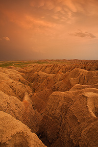 Orange hues from the last light of the setting sun illuminate storm clouds as they pass over Badlands National Park in South Dakota, dark clouds contrast with the desolate landscape. - South Dakota Photograph