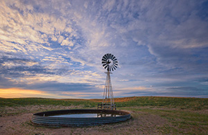 Dusk falls as clouds hover over a remote windmill in McKelvie National Forest in western Nebraska. - Nebraska Photograph
