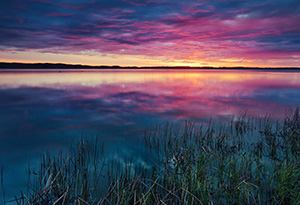 A small lake nestled in the Sandhills reflects the rising sun on a cool spring morning. - Nebraska Photograph
