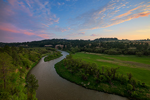 The Niobrara river west of Niobrara National Wildlife Refuge, snakes through a lush green valley on a beautiful spring morning. A cool breeze blew gently as the sun rose in the east illuminating the clouds in the sky. - Nebraska Photograph