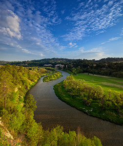 The Niobrara river, snakes through a lush green valley on a beautiful spring morning. A cool breeze blew gently as the sun rose in the east illuminating the clouds in the sky. - Nebraska Landscape Photograph