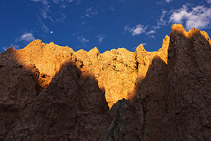 The first warm light of sunrise illuminates the erie rock formations deep in Badlands National Park as a waning moon gentle descends behind. - South Dakota Photograph