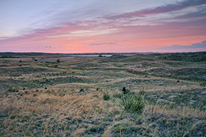 As the sun sets, the clouds ablaze with red hues over the undulating hills of central Nebraska. - Nebraska Photograph