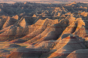 The warm light of the recently risen sun illuminates the Badlands of South Dakota in Badlands National Park. - South Dakota Photograph