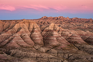 Pink clouds float above Badlands National Park while the rocky terrain below is bathed in the warm light just after sunset. - South Dakota Photograph