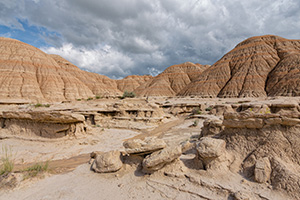 Afternoon clouds hover over the otherwordly landscape at Toadstool Geologic Park in Northwestern Nebraska. - Nebraska Photograph