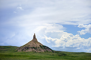 Afternoon storm clouds gather in the west billowing above Chimney Rock in the panhandle of Nebraska. - Nebraska Photograph