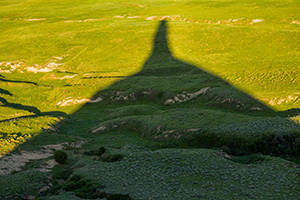 Chimney Rock's shadows stretches out across the plains as the sun dips low in the western sky. - Nebraska Photograph