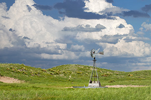 The sun shines on a windmill deep within the Sandhills of Nebraska as storm clouds roll in the distance. - Nebraska Photograph