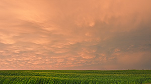 Passing ominous storm clouds reflect the red and orange hues of the sun 45 minutes after sunset. - Nebraska Photograph