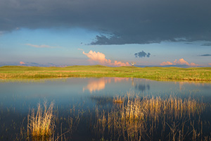 A windmill and storm clouds are reflected in a small lake in the Sandhills of Nebraska. - Nebraska Photograph