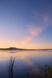 On a cool autumn morning, mist rises from Meng Reservoir on the Oglala Grassland while a single clouds hovers over the lake. - Nebraska Photograph