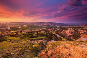 Above a bend in the Little Missouri River in the North Unit of Theodore Roosevelt National Park, clouds glow purple and orange as the sun just begins to rise above the horizon. - North Dakota Landscape Photograph