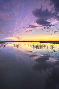 A scenic landscape photograph of a sunset reflected in the water at Jack Sinn WMA in eastern Nebraska. - Nebraska Photograph