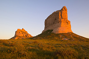 Jailhouse and Courthouse Rock both glow red with the first light at sunrise. - Nebraska Photograph