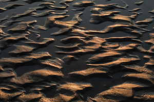 Capturing a photograph of a nature abstract, sand and water collide and intermingle to create interesting patterns along the banks of the Platte River in Eastern Nebraska. - Nebraska Photograph