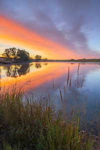 A landscape photograph of a sunrise reflected in a lake at Mahoney State Park, Nebraska. - Nebraska Photograph