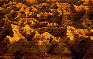 The late afternoon sun creates abstract shapes from the long shadows in the Badlands, South Dakota. - South Dakota Photograph