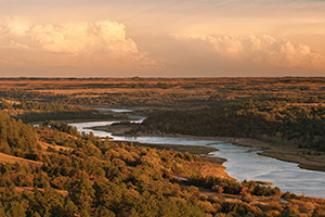 Storm clouds hover over the snaking Niobrara River near sunset in Keha Paha County in north central Nebraska. - Nebraska Photograph