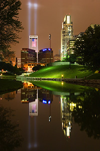 On September 11, 2006 Omaha, Nebraska paid tribute to the victims of 9/11 by hanging 2 large United States flags on the Woodmen tower and by shining two large lights into the sky. - Nebraska Photograph
