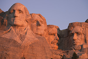 The warm sunrise light illuminates the faces with a reddish hue. - South Dakota Photograph