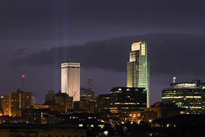 On September 11, 2006 Omaha, Nebraska paid tribute to the victims of 9/11 by hanging 2 large United States flags on the Woodmen tower and by shining two large lights into the sky.  This particular photo was taken during a spectacular fall lightning storm. - Nebraska Photograph