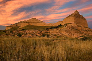 Scotts Bluff National Monument in western Nebraska.  Towering eight hundred feet above the North Platte River, Scotts Bluff has been a natural landmark for many peoples, and it served as the path marker for those on the Oregon, California, Mormon, and Pony Express Trails.  Scotts Bluff National Monument preserves 3,000 acres of unusual land formations which rise over the otherwise flat prairieland below. - Nebraska Photograph